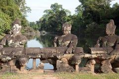 Monkey les gardiens reposant à l'entrée le sanctuaire au temple du 10ème siècle de Banteay Srei avec le mur découpé fleuri à l'ar Photo libre de droits