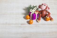 Monkey from plasticine with a gift and oranges for new year. Symbol of 2016, it is made of plasticine. As shot on a light wooden background, there is a place for Royalty Free Stock Image
