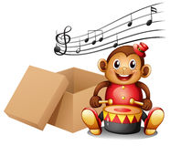 A monkey playing with musical notes and an empty box Stock Photography