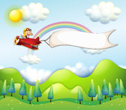 A monkey riding in a red airplane with an empty banner Royalty Free Stock Photos