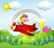 A monkey riding on a red plane with two balloons Stock Image