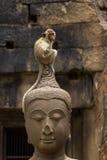 Monkey sitting perched on buddha head Royalty Free Stock Photography