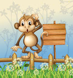 A monkey standing in a fence beside an empty board Stock Photo