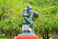 Monkey statue made of stone, in the pose of sensible over the human skull. Monkey Island stock photography