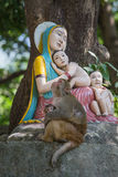 Monkey and statue Madonna and children Stock Photos