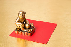 Monkey the symbol of the new year 2016 , and red envelope. Monkey the symbol of the chinese new year 2016, and red envelope on a gold background stock photography