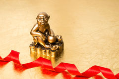 Monkey the symbol of the new year 2016, and red satin ribbon Royalty Free Stock Photos
