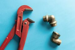 A monkey wrench on the blue background with some fitting connectors. for design and decoration.  royalty free stock photos
