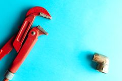 A monkey wrench on the blue background with some fitting connectors. for design and decoration.  royalty free stock photography