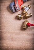 Monkey wrench and brass plumbing fixtures  on Royalty Free Stock Images