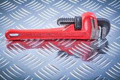 Monkey wrench on channeled metal background construction concept Stock Image