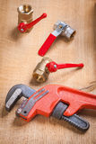 Monkey wrench and plumbing fixtures on wooden board Stock Image