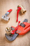 Monkey wrench with plumbing fixtures on wooden board Stock Images