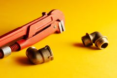 A monkey wrench on the yellow background with some fitting connectors. for design and decoration.  stock photography