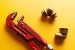 A monkey wrench on the yellow background with some fitting connectors. for design and decoration.  royalty free stock images