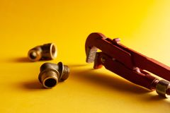 A monkey wrench on the yellow background with some fitting connectors. for design and decoration.  stock photo