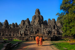 The monks in the ancient stone faces of Bayon temple, Cambodia Royalty Free Stock Photo