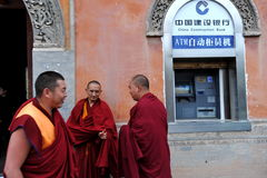 Monks and ATM. Tibetan monks discussing near chinese ATM machine Stock Image