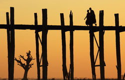 U-Bein bridge at sunset, Myanmar. Monks crossing the U-Bein bridge at sunset, Amarapura, Myanmar (Burma Stock Images