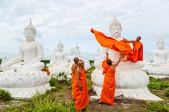 Monks dressing one of White Buddha Image with robes Royalty Free Stock Photography