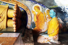 Monks and feet. Monks seated near Buddha's feet Stock Image