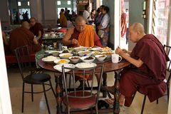 Monks at the Mahagandayon Monastery in Amarapura Myanmar. Buddhist monks in traditional robes are eating in the dining hall at the Mahagandayon Monastery in stock photo