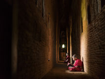 Monks meditating reading book in the temple Royalty Free Stock Images