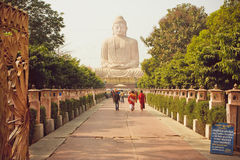 Monks and other people rushing to 24.38 metre Buddha statue Royalty Free Stock Image