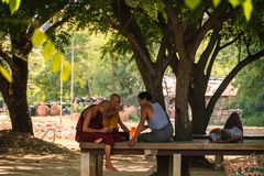 Monks and People taking under tree. Bagan, Myanmar, 11 August 2018 stock images