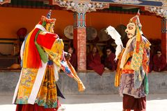 Monks perform a masked and costumed sacred dance of Tibetan Buddhism, another monks play ritual music during the Cham Dance Festiv stock photos