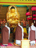 Monks pray. Monks stand in front of the Buddha in the mausoleum and pray Royalty Free Stock Image