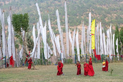 Monks and prayer flags, Chimi Lhakang, Punakha, Bhutan. Young student, who study Buddhism, are playing in the field with prayer flags in the background at the Royalty Free Stock Images