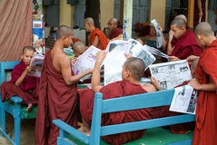 Monks reading newsparers at the  Shwe in Bin Kyaung monastery of Royalty Free Stock Image