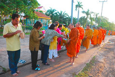 Monks Receiving Rice Offering Stock Photo