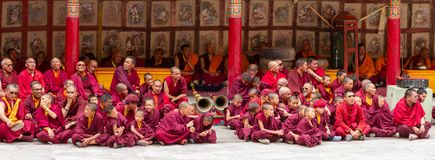 Monks, ritual drummers, trumpeters with musical instruments as spectators at the Cham Dance Festival of Tibetan Buddhism in Hemis royalty free stock image