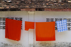 Monks' robes hanging at a temple wall Stock Photos