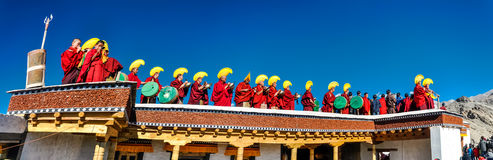 Monks in row on roof in Ladakh. Thiksey, Ladakh - circa November 2011: Monks with traditional big yellow hats stand on roof in row and play musical instruments Stock Photo