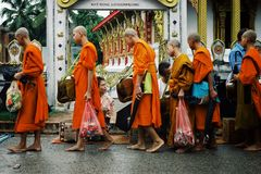 Monks during their early morning round around the town to collect their alms. Luang Prabang / Laos - JUL 06 2011: monks during their early morning round around royalty free stock image