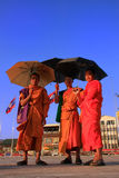 Monks with umbrellas walking near Mekong river Stock Image