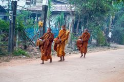 Monks walk in the early morning in the Isan village in Sakon Nakhon province, Thailand stock photography