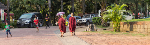 Monks walk near the Kandawgyi Lake in Yangon, Myanmar Stock Photos