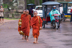 Monks walk by the road in front of the Angkor Thom South gate in Siem Reap, Cambodia. Royalty Free Stock Image