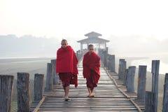 Monks walk on wood brigde Royalty Free Stock Image