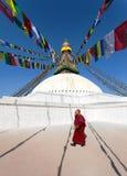 Monks walking around Boudhanath stupa Stock Image
