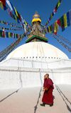 Monks walking around Boudhanath stupa Stock Image