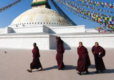 Monks walking around Boudhanath stupa Stock Photography