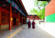 Monks walking inside the lama temple. Buddhist monks walking inside Yonghegong Lamasery in Beijing China Royalty Free Stock Photography