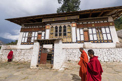Monks walking past building in Rinpung dzong Royalty Free Stock Photo