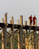 Monks walking on U Bein Bridge in Myanmar. Two monks walking over the famous U Bein Bridge across the Taungthaman Lake in Mandalay, Myanmar. It's a famous Royalty Free Stock Photos