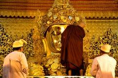 Monks wash the face and brush the teeth of the Buddha image at Maha Myat Muni Stock Photography